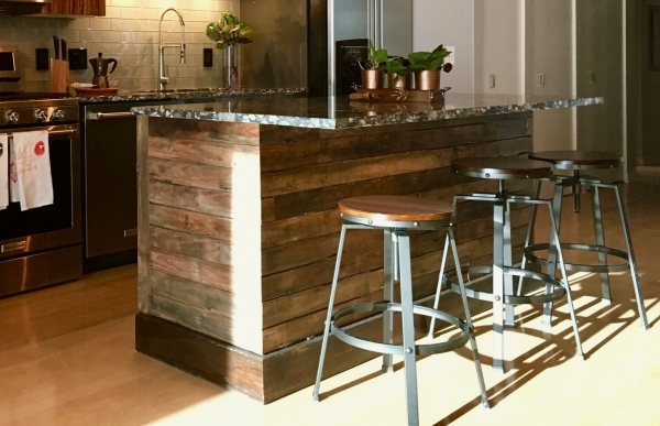 Reclaimed wood, custom-made, kitchen island with pebble print marble top. A rustic touch to a modern space